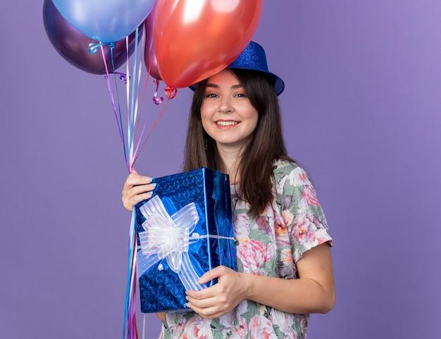 Sorridente giovane bella donna che indossa cappello da festa che tiene palloncini con scatola regalo isolata sulla parete blu