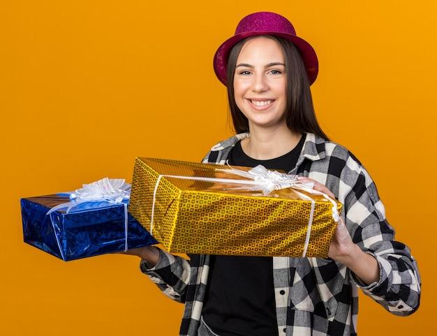 Sorridente giovane bella donna che indossa cappello da festa tenendo scatole regalo isolate su parete arancione