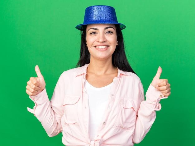 Sorridente giovane bella donna che indossa un cappello da festa che mostra i pollici in su