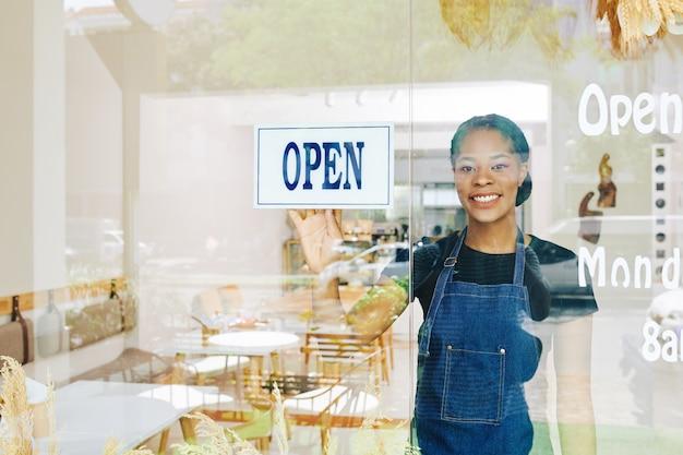 Sorridente giovane proprietario di un piccolo caffè nero felice di aprire una panetteria dopo il periodo di quarantena