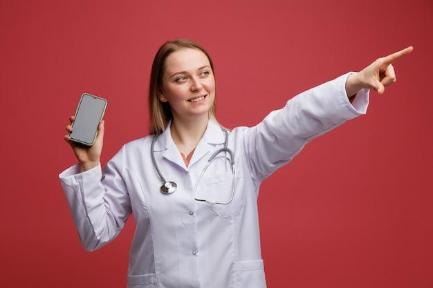 Sorridente giovane bionda femmina medico indossa abito medico e stetoscopio intorno al collo tenendo il telefono cellulare alla ricerca e rivolto verso l'alto all'angolo