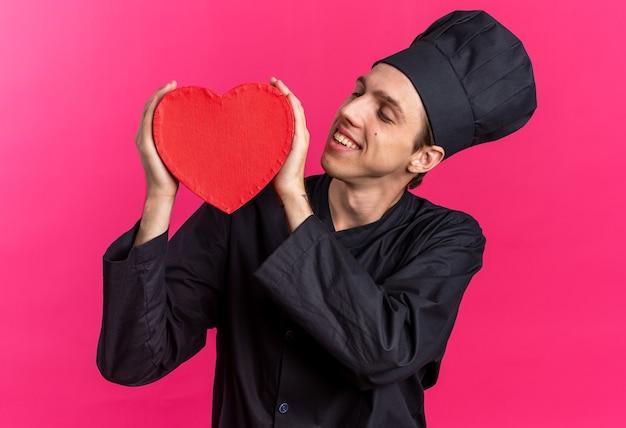 Sorridente giovane cuoco maschio biondo in uniforme da chef e berretto che tiene a forma di cuore con entrambe le mani guardandolo isolato su parete rosa