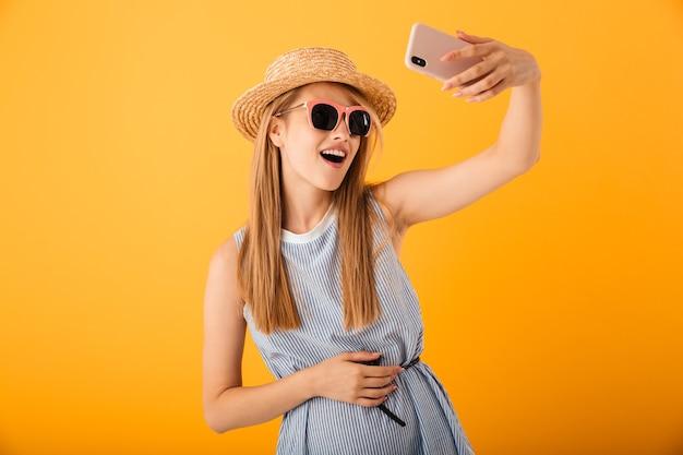 Sorridente giovane donna bionda in cappello estivo