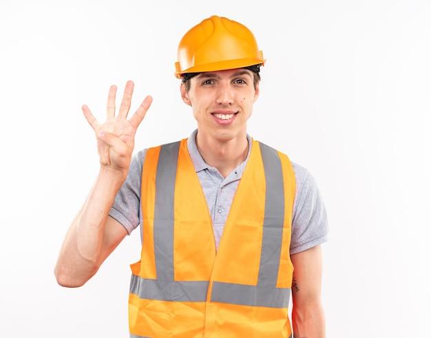 Sorridente giovane costruttore in uniforme che mostra quattro isolati sul muro bianco