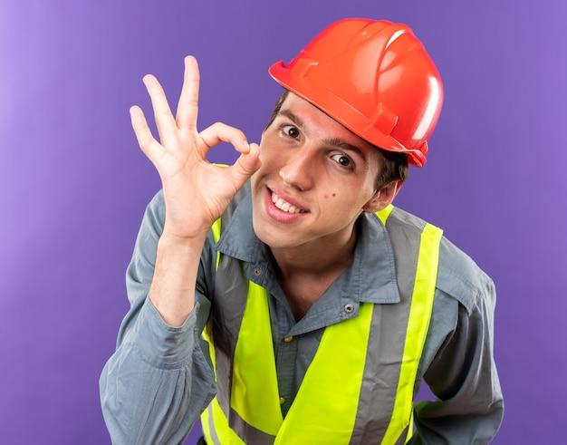 Sorridente giovane costruttore in uniforme che mostra gesto ok