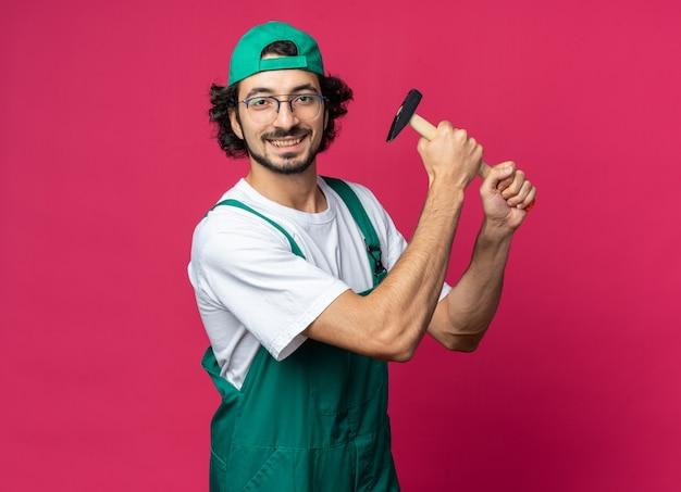 Sorridente giovane costruttore uomo che indossa l'uniforme con cappello che tiene martello