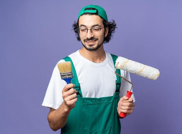 Sorridente giovane costruttore che indossa un'uniforme con cappuccio che tiene la spazzola a rullo e guarda il pennello in mano