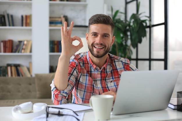 Sorridente giovane uomo d'affari con videochiamata in ufficio a casa.