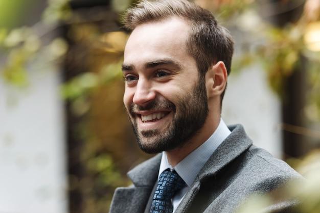 Sorridente giovane uomo d'affari che indossa tuta camminare all'aperto