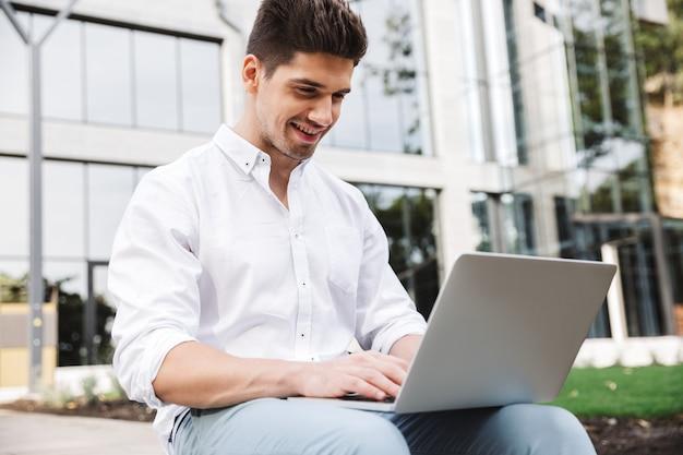 Sorridente giovane uomo d'affari che lavora al computer portatile