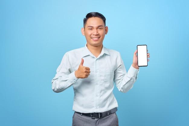 Sorridente giovane uomo d'affari che mostra lo schermo vuoto dello smartphone e fa i pollici in su su sfondo blu