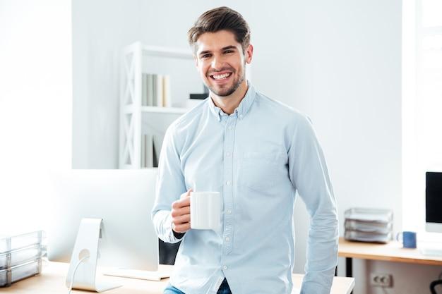Sorridente giovane uomo d'affari in piedi e bevendo caffè in ufficio