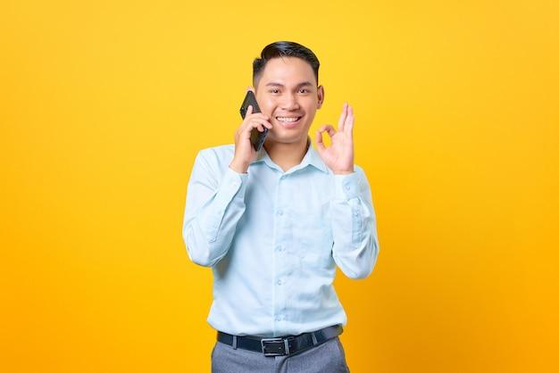 Sorridente giovane uomo d'affari che parla su uno smartphone e fa un gesto ok su sfondo giallo