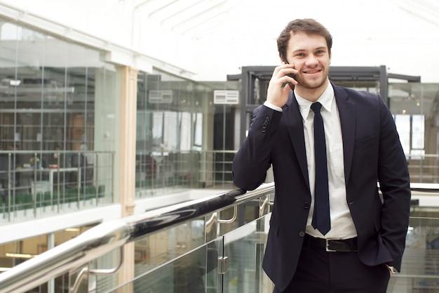 Giovane uomo d'affari sorridente che parla sullo smartphone in mani.