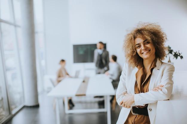 Sorridente giovane imprenditrice in piedi in un ufficio moderno