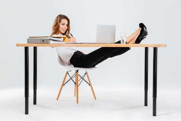 Sorridente giovane imprenditrice utilizzando laptop e scrivere con le gambe sul tavolo su sfondo bianco