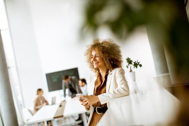 Sorridente giovane imprenditrice utilizzando il telefono cellulare in un ufficio moderno