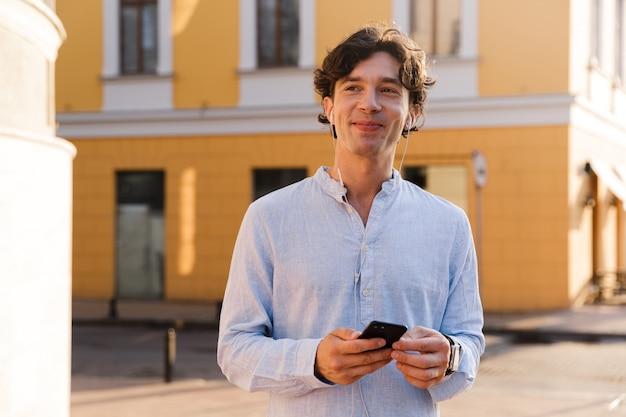 Sorridente giovane uomo casual tenendo il telefono cellulare