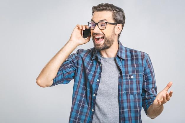 Giovane uomo casuale sorridente che parla sul telefono sulla parete grigia. isolato.