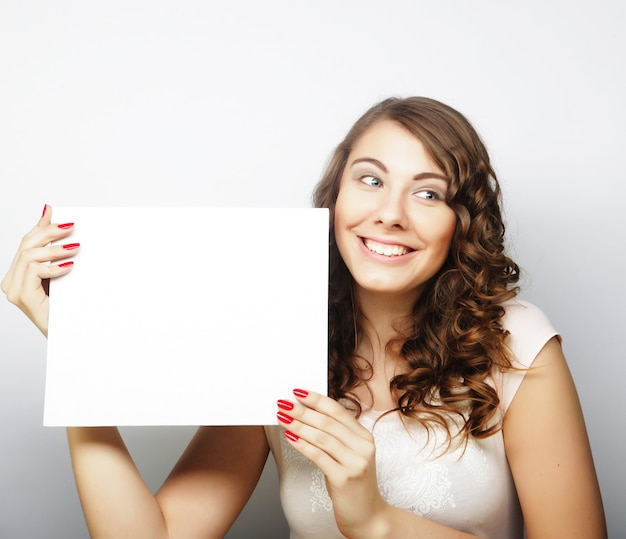 Sorridente giovane donna in stile casual che mostra cartello bianco, su sfondo grigio isolato