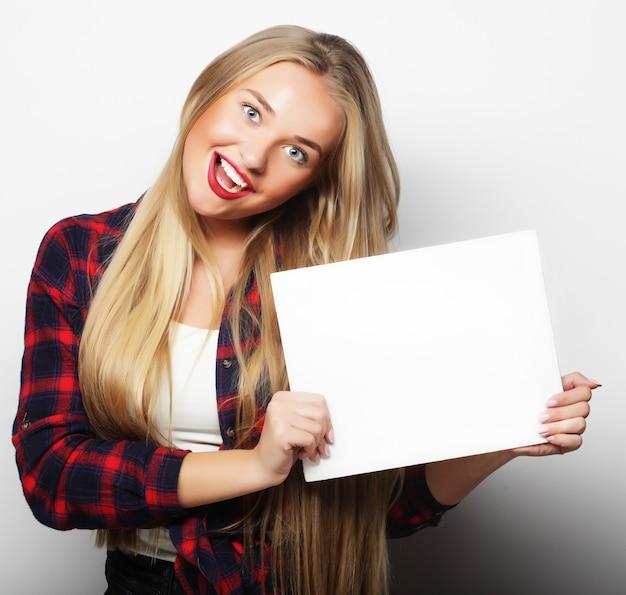 Sorridente giovane donna in stile casual che mostra cartello bianco, su sfondo bianco isolato