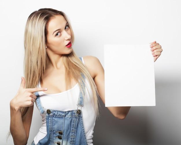Sorridente giovane donna stile casual che mostra cartello bianco, su sfondo bianco isolato