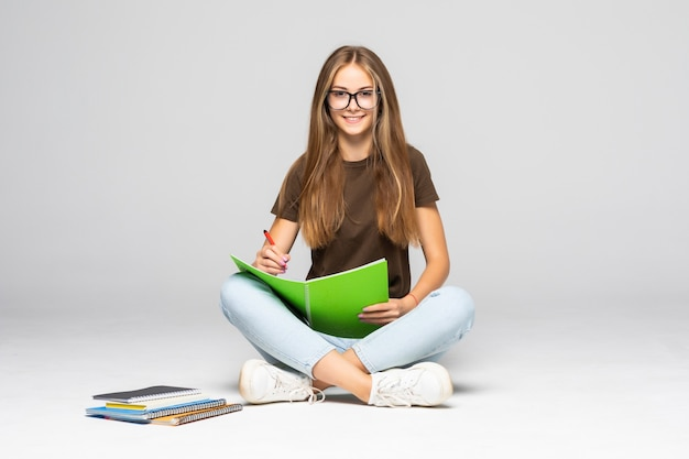 Sorridente giovane donna casual scrivendo sul suo blocco note mentre era seduto sul muro bianco