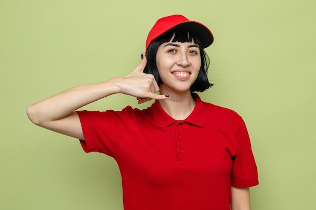 Sorridente giovane ragazza delle consegne caucasica che gesturing chiamami segno
