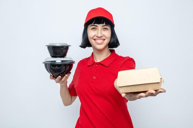 Sorridente giovane ragazza caucasica delle consegne che tiene in mano contenitori per alimenti e imballaggi guardando la parte anteriore