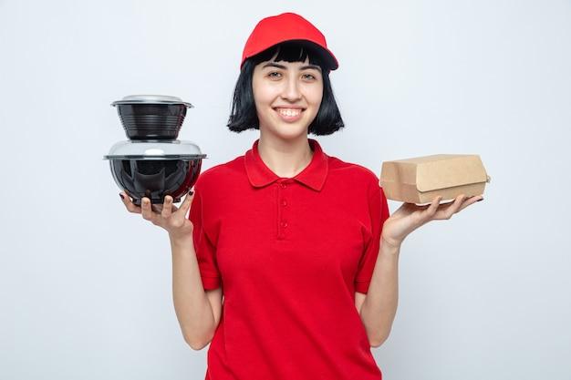 Sorridente giovane ragazza caucasica delle consegne che tiene in mano contenitori e imballaggi per alimenti