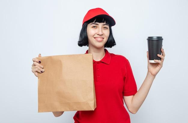 Sorridente giovane ragazza delle consegne caucasica che tiene in mano imballaggi per alimenti e bicchiere di carta