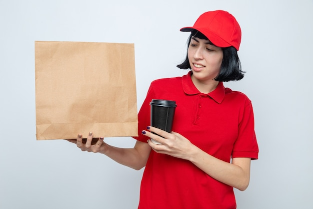 Sorridente giovane ragazza caucasica delle consegne che tiene in mano un bicchiere di carta e guarda l'imballaggio del cibo