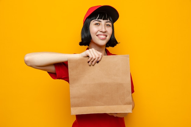 Sorridente giovane ragazza delle consegne caucasica che tiene in mano un imballaggio alimentare di carta