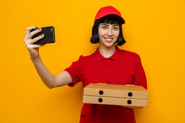 Sorridente giovane ragazza delle consegne caucasica che tiene in mano scatole per pizza e telefono