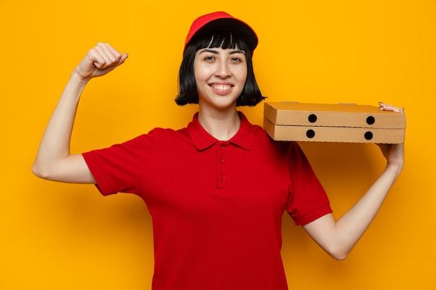 Sorridente giovane caucasica ragazza delle consegne tenendo scatole per pizza e tendendo i suoi bicipiti