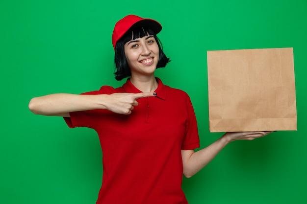 Sorridente giovane ragazza caucasica delle consegne che tiene e indica l'imballaggio di carta per alimenti