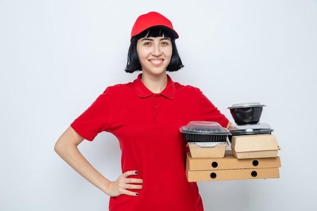 Sorridente giovane ragazza caucasica delle consegne che si mette la mano sulla vita e tiene in mano contenitori per alimenti e imballaggi su scatole per pizza