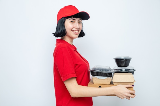 Sorridente giovane caucasica ragazza delle consegne in piedi lateralmente tenendo contenitori per alimenti e imballaggi su scatole per pizza