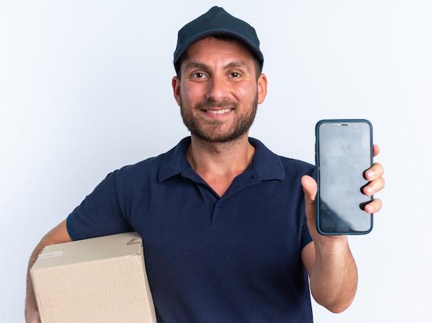 Sorridente giovane fattorino caucasico in uniforme blu e cappuccio che tiene una scatola di cartone guardando la telecamera che allunga il telefono cellulare verso la telecamera isolata sul muro bianco