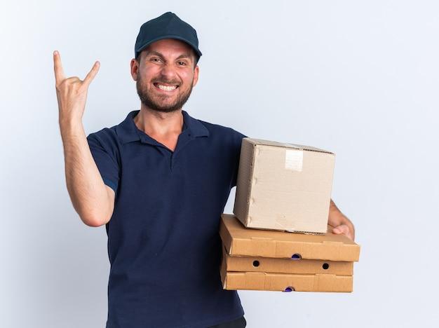 Sorridente giovane fattorino caucasico in uniforme blu e berretto con scatola di cartone e pacchetti di pizza guardando la telecamera facendo segno rock isolato su muro bianco