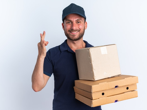 Sorridente giovane fattorino caucasico in uniforme blu e berretto che guarda la telecamera che tiene in mano una scatola di cartone e pacchetti di pizza che ne mostrano tre con la mano isolata sul muro bianco