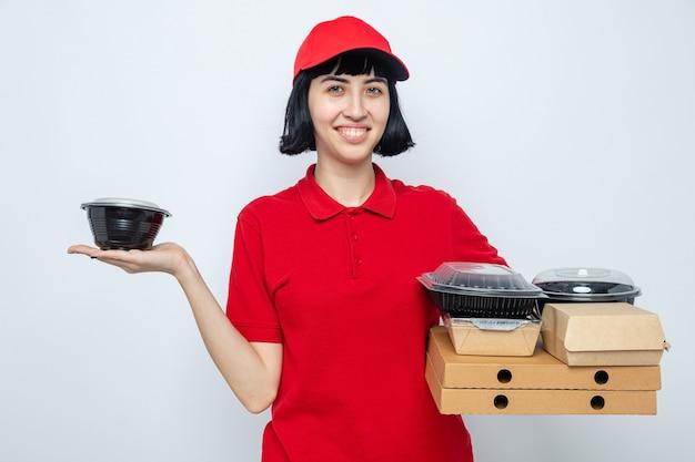 Sorridente giovane donna delle consegne caucasica che tiene in mano un contenitore per alimenti e scatole per pizza