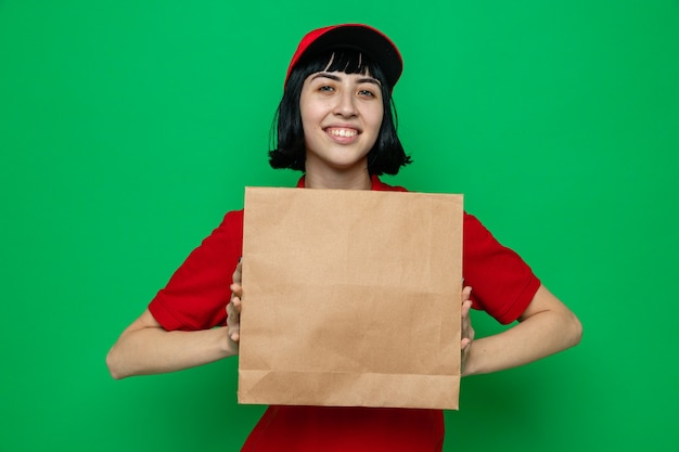 Sorridente giovane donna di consegna caucasica che tiene in mano un sacchetto di carta per alimenti e guarda