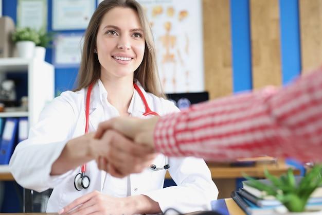 Sorridente giovane dottoressa caucasica che stringe la mano con il saluto e l'incontro con il paziente in ospedale