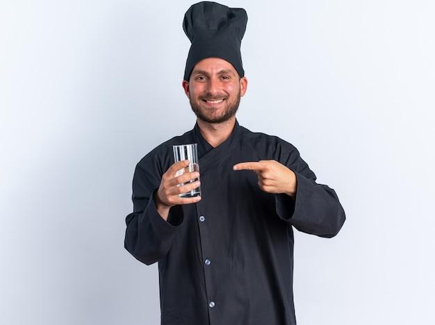 Sorridente giovane maschio caucasico cuoco in uniforme da chef e berretto che tiene e indica un bicchiere d'acqua guardando la telecamera isolata sul muro bianco