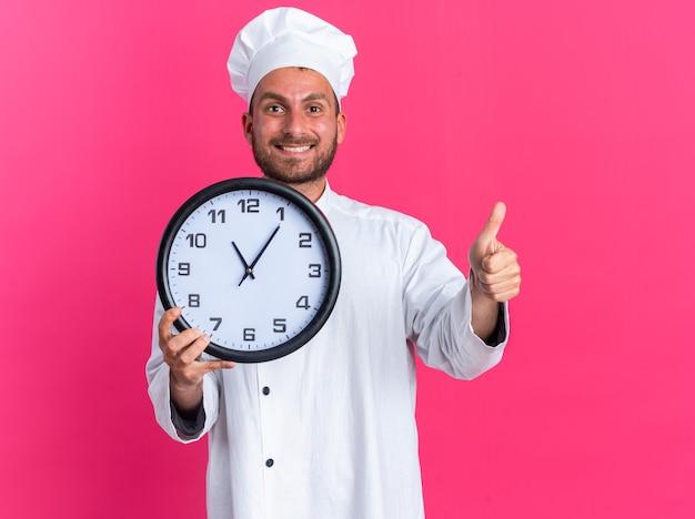 Sorridente giovane maschio caucasico cuoco in uniforme da chef e berretto che mostra orologio e pollice in su guardando la telecamera isolata sulla parete rosa