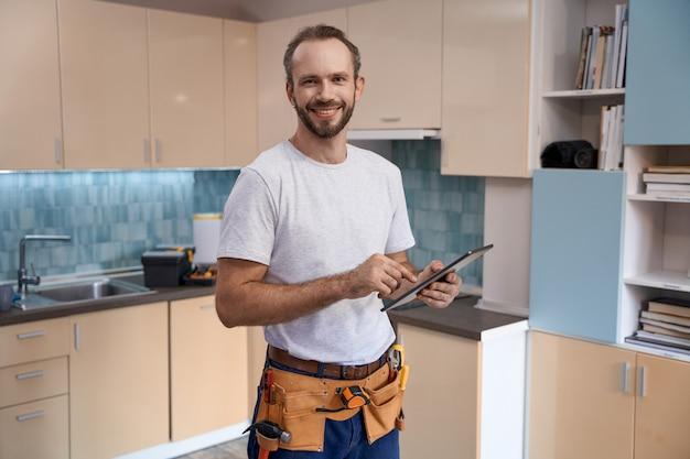 Sorridente giovane lavoratore maschio caucasico con tablet durante il lavoro in cucina