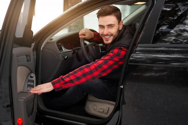 Giovane uomo caucasico sorridente. inverno. autista