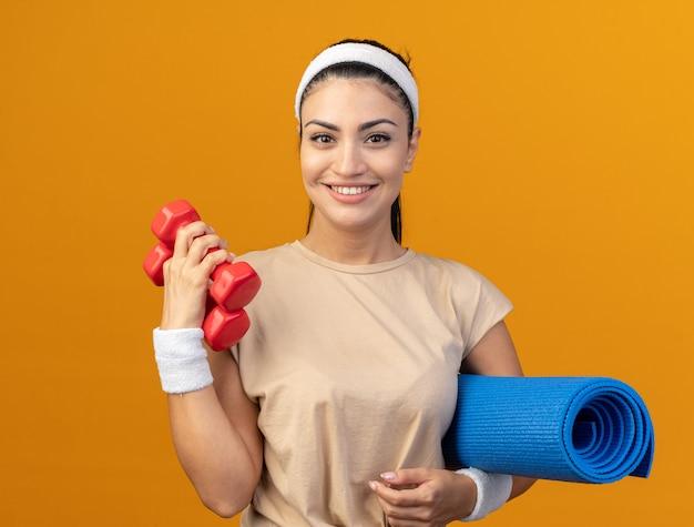 Sorridente giovane ragazza sportiva caucasica che indossa fascia e braccialetti che tengono tappetino fitness e manubri isolati su parete arancione
