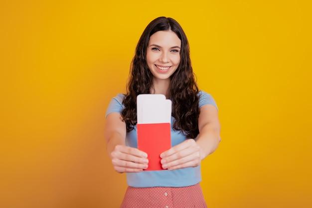 La giovane donna allegra sorridente tiene la carta d'imbarco dei biglietti del passaporto isolata sul fondo della parete di colore giallo brillante